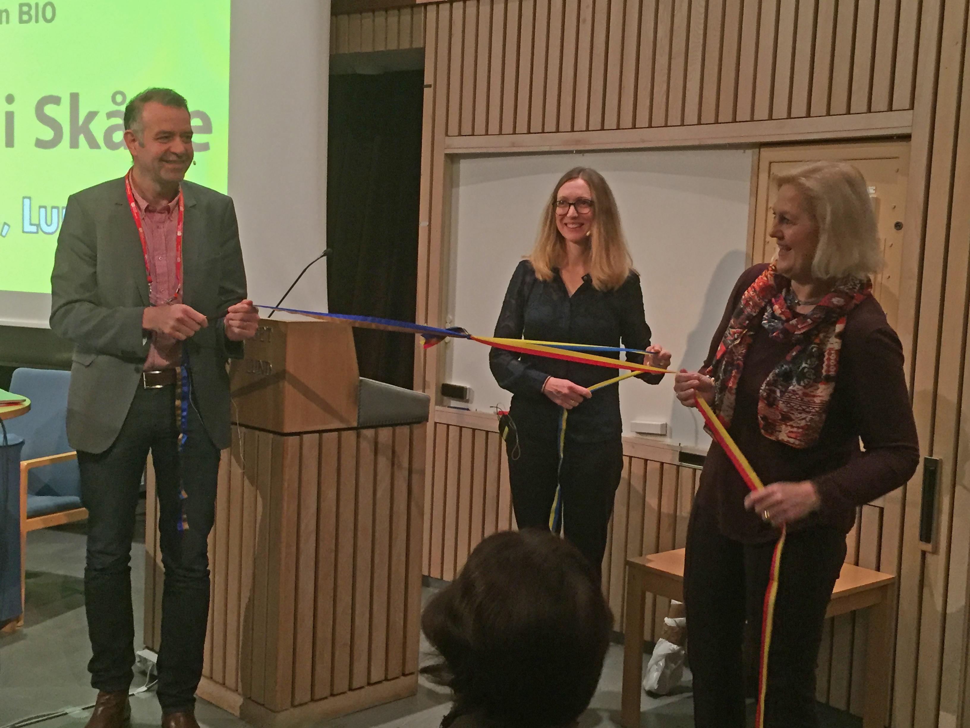 Tomas Jansson, föreståndare för Medicon Bridge, (t.v.) knyter ihop invigningsband tillsammans med Sara Gunnerås, SwedenBIO (mitten), och Hannie Lundgren, Styrelseordförande för Medicon Bridge och forskningschef Region Skåne (t.h.)